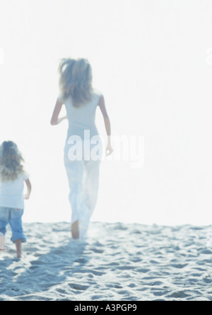 Woman and girl running on beach Banque D'Images