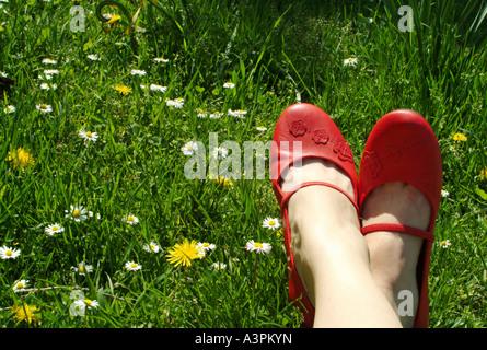 Les pieds de chaussures rouges sur un pré Banque D'Images