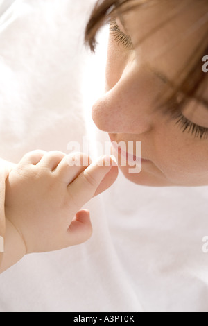 Mother kissing baby's hand Banque D'Images