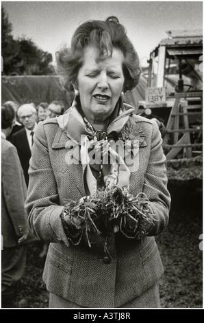 Mme Thatcher face comique tirant comme elle prend du fumier sur une ferme Banque D'Images