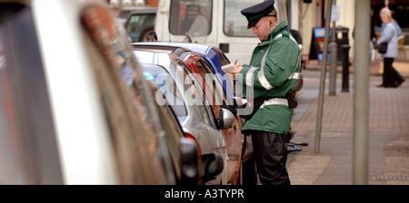 Un gardien de la circulation distribue un ticket de parking dans une rue animée de Brighton. Banque D'Images