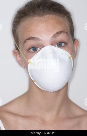 Une jeune femme avec un masque de visage regardant la caméra Banque D'Images