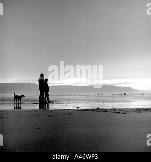 Couple romantique avec leur chien sur la plage de Bude Cornwall Banque D'Images