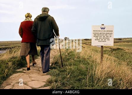 Deux personnes marchant vers la côte avec un panneau d'avertissement de l'érosion côtière Norfolk Broads Angleterre Banque D'Images