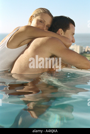 Woman embracing man in pool Banque D'Images