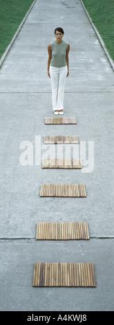Femme debout en face de chemin de rectangles en bois Banque D'Images