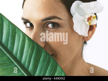 Femme avec orchidée derrière l'oreille, la feuille de palmier couvrant partiellement le visage, close-up Banque D'Images
