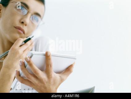 Woman on phone holding le bloc-notes et stylo Banque D'Images