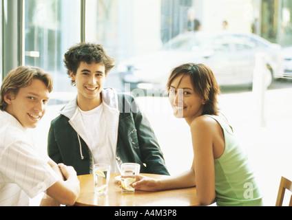 Groupe de jeunes gens assis à table à café, smiling at camera Banque D'Images