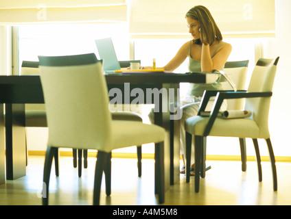 Jeune femme à la table de travail, le télétravail Banque D'Images
