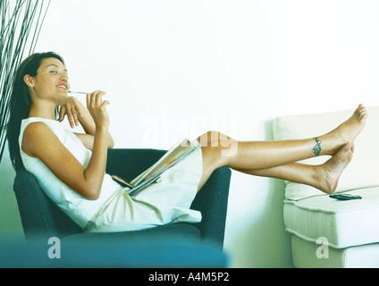 Femme assise, sur le côté, fauteuil, pleine longueur Banque D'Images