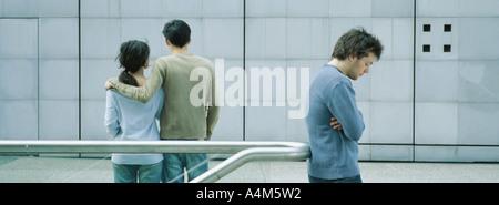 Jeune couple en train de marcher ensemble, jeune homme debout avec les bras croisés en premier plan Banque D'Images