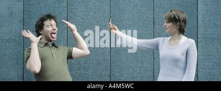 Jeune homme faisant face en tant que jeune femme avec lui des photographies téléphone appareil photo Banque D'Images