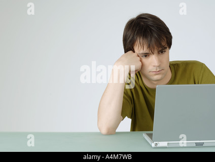 Young man using laptop, s'appuyant sur le coude Banque D'Images