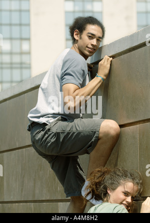 Young man and woman climbing wall Banque D'Images