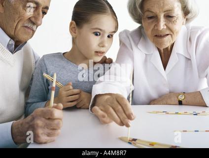 Les grands-parents et fille assise à table jouant pick up sticks