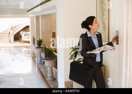 Businesswoman reading newspaper dans l'attente d'ascenseur Banque D'Images
