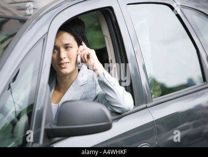 Businesswoman using cell phone in car Banque D'Images
