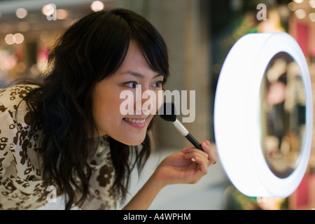 Young woman applying makeup in shopping mall Banque D'Images