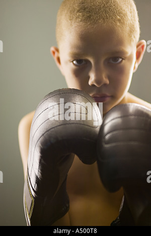 Boy wearing boxing gloves Banque D'Images