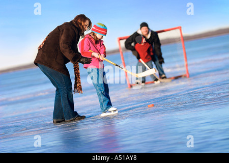 Family playing shinny hockey Banque D'Images