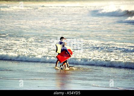 Père et Fils SE PRÉPARER À ALLER POUR UN SURF COFFS HARBOUR NSW Australie Banque D'Images
