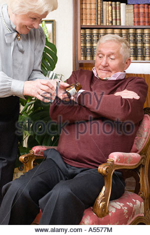 Femme essayant de donner les comprimés de mari Banque D'Images