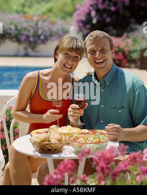 Jeune couple de manger et boire du vin sur la terrasse de piscine