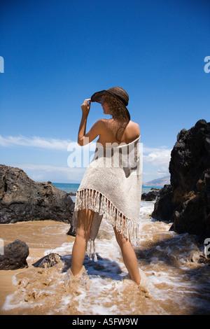 Les jeunes femelles adultes de race blanche dans l'eau sur la plage chapeau basculant Banque D'Images