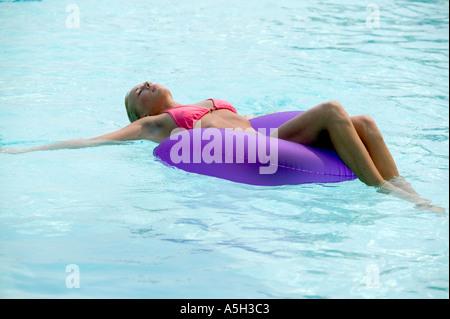 Une jeune femme flottant dans une piscine Banque D'Images