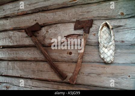 Axes et une vieille chaussure faite d'écorce bich accroché au mur d'une maison bloc gris Banque D'Images