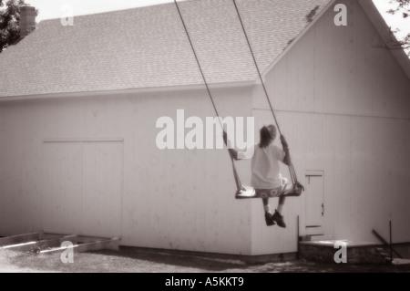 Fille sur rope swing sur farm Banque D'Images