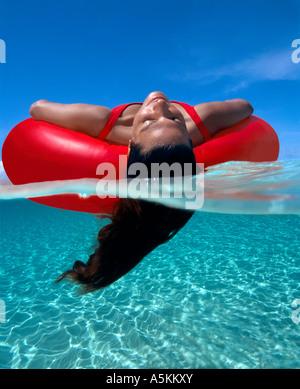 Banc de Grand Cayman en vertu d'une femme rouge flotte sur tube inter avec ses cheveux dans l'eau Banque D'Images