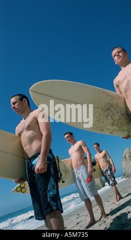 Les adolescents et les étudiants avec des planches de poser dans la chaleur du soleil sur une plage de la californie Banque D'Images