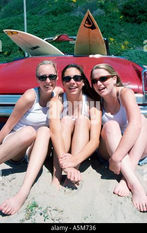 Les adolescentes et les étudiants avec des planches de poser dans la chaleur du soleil sur une plage de la californie Banque D'Images