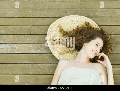 Femme enveloppée dans une serviette, allongé sur le pont, smiling Banque D'Images