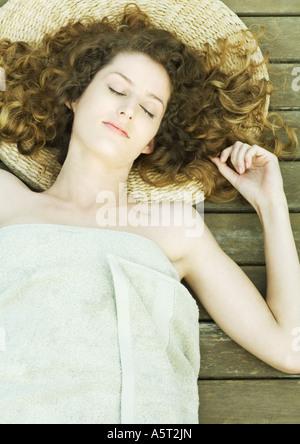 Femme enveloppée dans une serviette, allongé sur le pont, les yeux fermés Banque D'Images