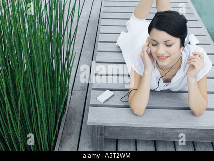 Woman lying on lounge chair listening to headphones Banque D'Images