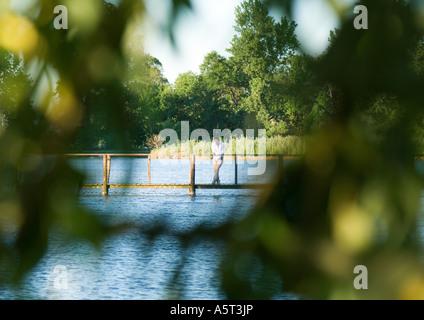 Homme debout sur la passerelle au-dessus de fleuve, dans la distance, vu à travers les feuilles en avant-plan flou Banque D'Images