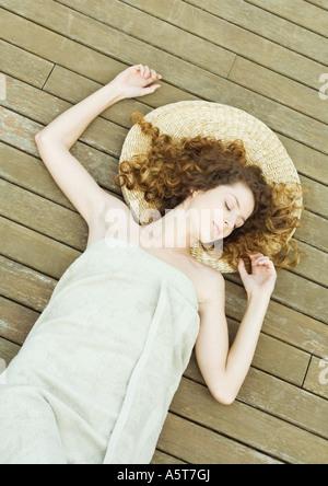 Femme couchée sur le pont, enveloppé dans une serviette, tête sur mat Banque D'Images