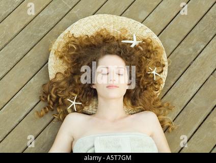 Femme couchée sur le pont, enveloppé dans une serviette, tête sur mat, étoiles dans les cheveux Banque D'Images