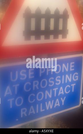 Roadsign atmosphérique dénotant le passage à niveau ferroviaire gate avec de mots Utilisez téléphone au croisement Banque D'Images
