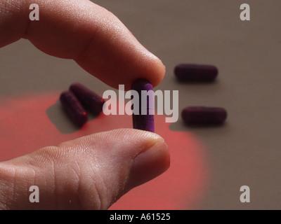 Libre de doigts holding Medicine Capsules de Nexium du flou des pilules dans l'arrière-plan Banque D'Images