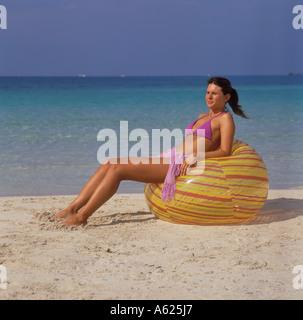 Scène de plage d'Es Trenc Platja de Trenc Mallorca en SE fille en bikini violet reposant sur de gros ballons de Banque D'Images