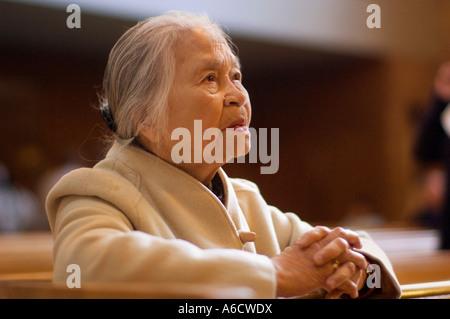 Femme en prière à l'intérieur de Église Banque D'Images