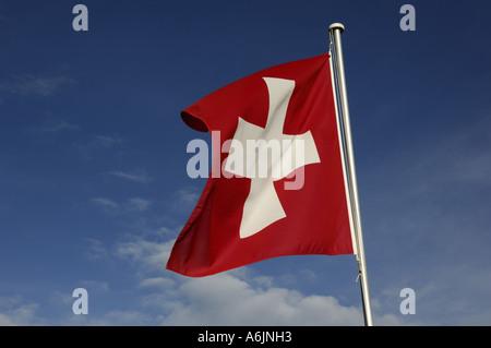 Drapeau suisse à coups de vent à ciel bleu, Suisse Banque D'Images