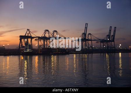 Grues à quai qui se profile à l'aube avec projecteurs & ciel mauve reflétée dans l'eau à Port Kelang pour Kuala Banque D'Images