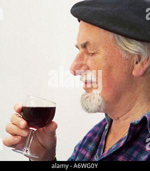 Monsieur le vieil homme Senior citizen au béret tenant un verre de dégustation de vin rouge Banque D'Images