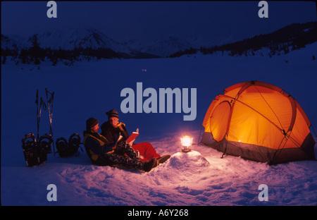 Les Adultes Le Camping d'hiver et de lecture w Lantern KP AK Banque D'Images