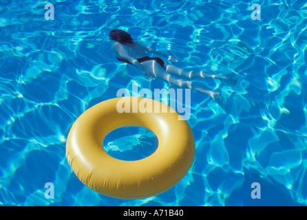 Tube intérieur jaune en piscine avec en arrière-plan sous-marine femme parution modèle droit Banque D'Images